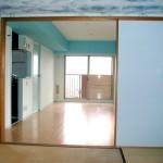 和室から見たリビング。梁に濃い水色の壁紙。キッチンの壁は穴を開けて風通りを良くしました。玄関の空間は濃い青ですが、ここは穏やかな水色の空間を意識しました。